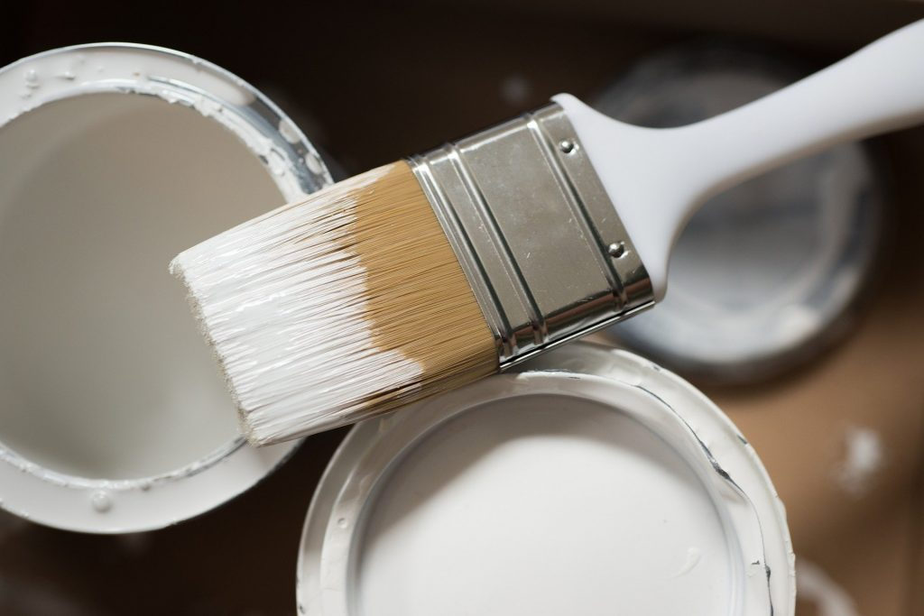 white paint brush and cans